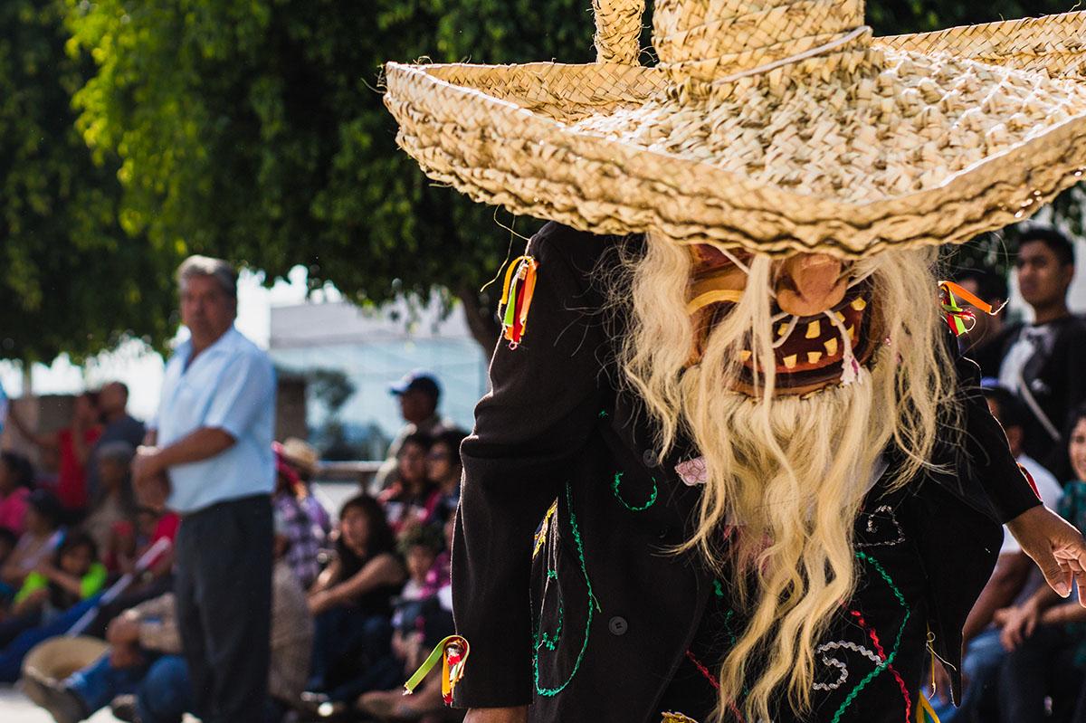 Viejos rancios vestidos vestidos con grandes máscaras y sombreros